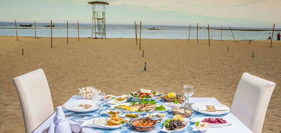 Fish mezes on a table laid out on the beach